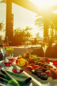 Sunlight over the restaurant table with sushi dish and champagne glasses. Vertical image