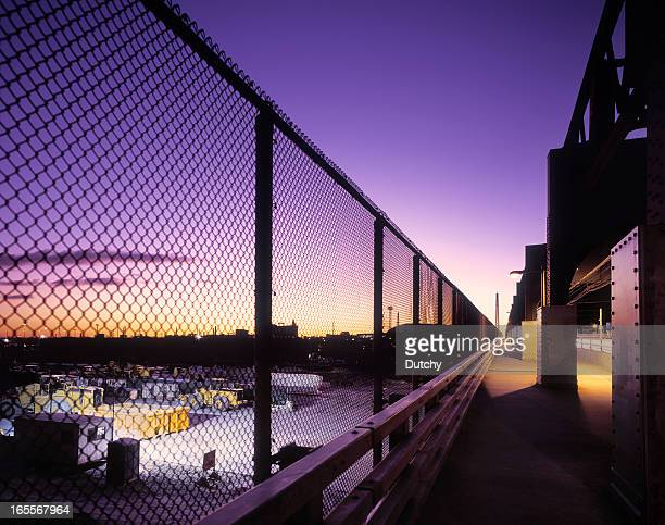 Sunrise at a bridge with fence and industrial estate.