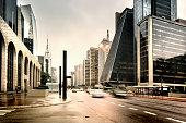 Photo of Paulista Avenue, in Sao Paulo city, Brazil.  Sunrise moment. Blurred motion cars. Vertical orientated.