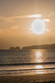 Sun rising over Ballard Down and Old Harry Rocks viewed from Studland Beach