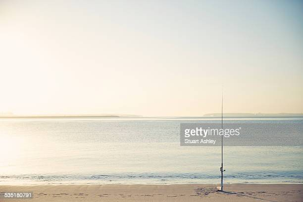 Sunrise fishing and fishing rod on beach