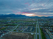 Aerial view at sunrise of Bozeman Montana. Mountain range and city lights in the distance. View looking down Oak St. as the sun comes up.