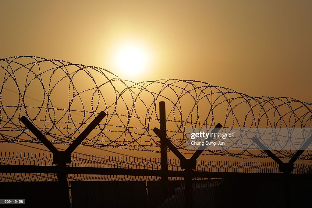 A sunrise is seen through a barbed-wire fence at the military check point, near the Demilitarized zone (DMZ) separating South and North Korea on February 11, 2016 in Paju, South Korea. South Korea announced on February 10, 2016 that the country would close an industrial complex jointly ran with North Korea, as the strongest response for North's recent nuclear test and rocket launch.