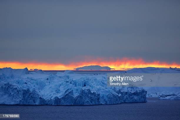 Sunrise over blue icebergs in Western Greenland
