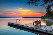Bench sitting on the dock as a colourful sunrise lights up the sky over Clear Lake, in Riding Mountain National Park, Manitoba Canada