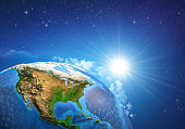 Rising sun over the Earth in deep space, focused on the United States of America.