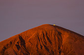 Sunrise light reflected on Croagh Patrick mountain, turning it golden red. Chapel clearly visible at the top.