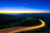 Sunrise scence of car light trail to the top with curve of road at Doi Inthanon National park in Chiang Mai Province, Thailand.