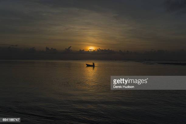 A sunrise view of the Indian ocean at Msambweni a fishermen in his dugout canoe sets off to catch the high tide The small fishing town and...