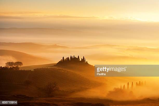 Sunrise with rays over the Misty valleys in Tuscany,Italy.