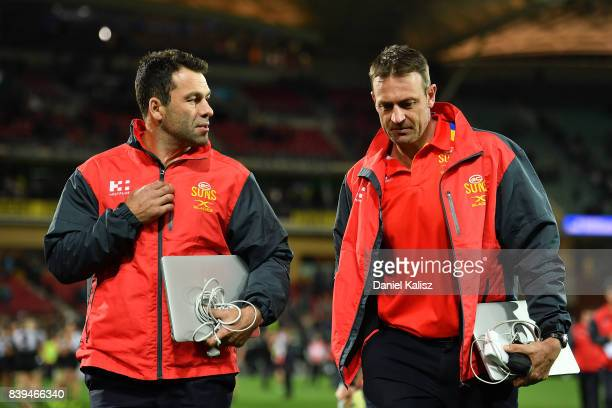 Suns interim head coach Dean Solomon and Suns assistant coach Matthew Primus walk from the field after during the round 23 AFL match between the Port...