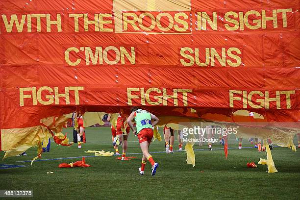 Suns players run through their banner during the round seven AFL match between the North Melbourne Kangaroos and the Gold Coast Suns at Etihad...