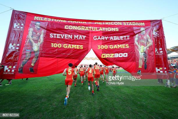 Suns run through the team banner during the round 15 the Gold Coast Suns and the North Melbourne Kangaroos at Metricon Stadium on July 1 2017 in Gold...
