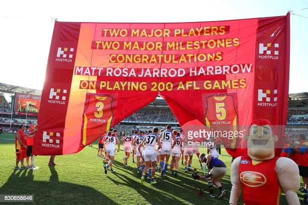 Suns run through the team banner during the round 21 AFL match between the Brisbane Lions and the Gold Coast Suns at The Gabba on August 12 2017 in...