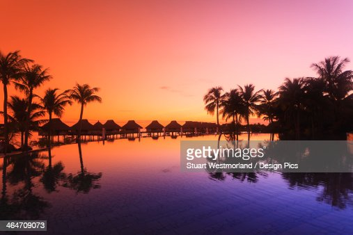 Sunset And Palm Trees Reflecting In A Pool At The Bora Bora Nui Resort And Spa