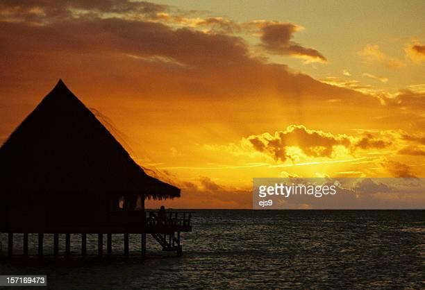 Coucher du soleil et un bungalow tropical