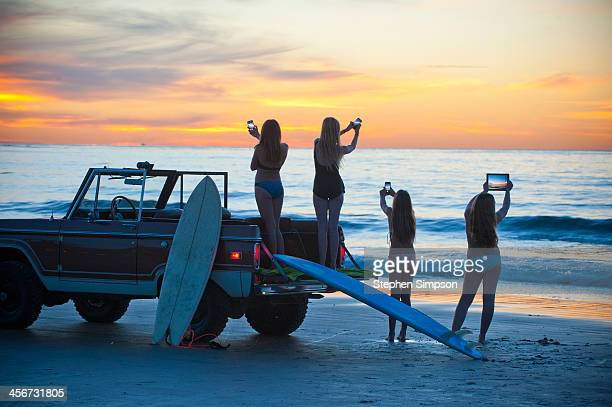 sunset at beach, girls with smart phones & tablet