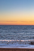 Sunset at Brighton Beach, with an offshore wind farm on the horizon