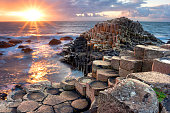 People visiting Giant s Causeway at the sunset in North Antrim, Northern Ireland
