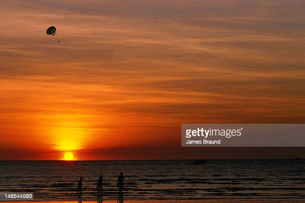 Sunset at Mindil Beach. Paraglider and bathers take in the view.