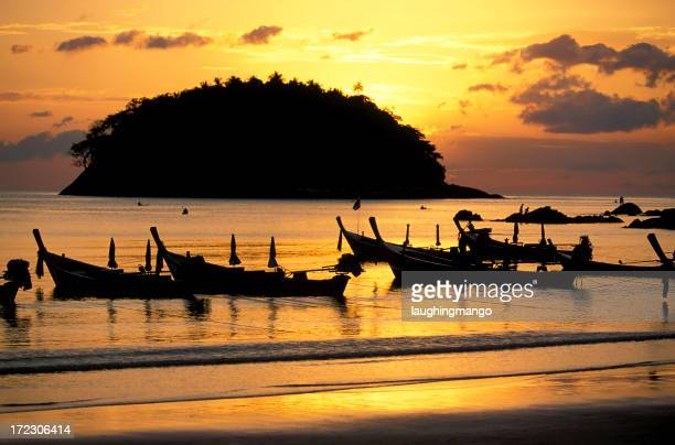 Sunset at Phuket beach with silhouettes of boats and island