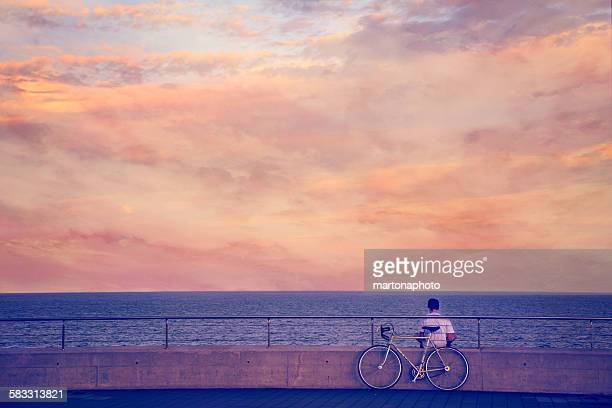 Sunset at sea, with sitting back boy and his bike