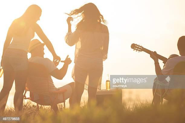 Coucher de soleil sur la plage avec un groupe d'amis