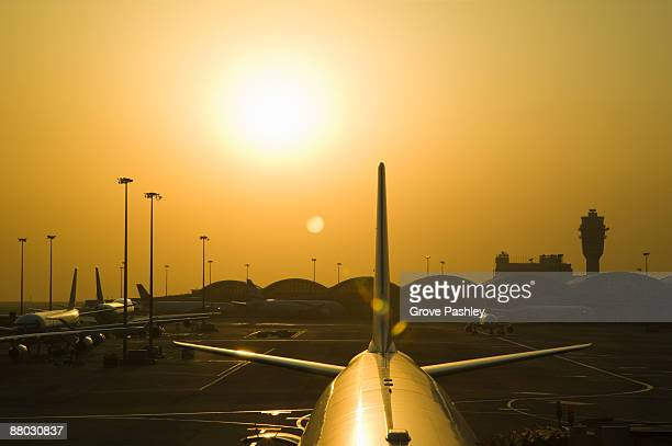 Sunset behind parked commercial airplane