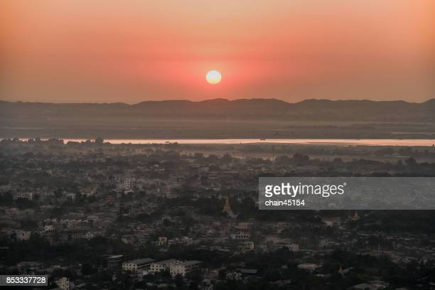 Sunset behind the mountains with temple and pagoda at Mandalay hill in Myanmar.