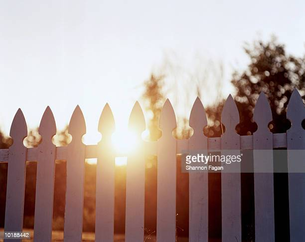 Sunset behind white picket fence