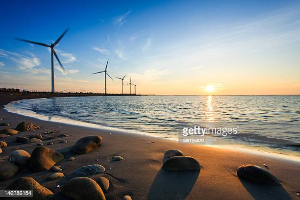 Sunset by beach with wind turbines
