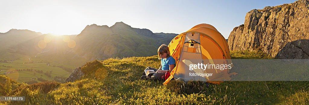 Sunset child camping on idyllic mountain top : Stock Photo