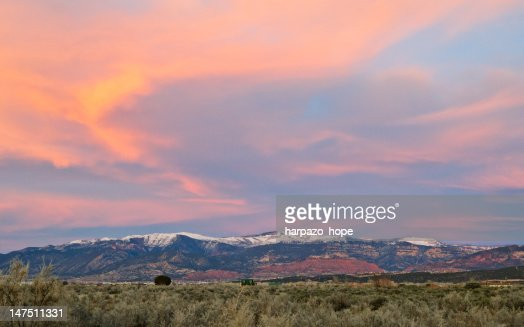 Sunset clouds above snowy redrock mountains : Stock Photo