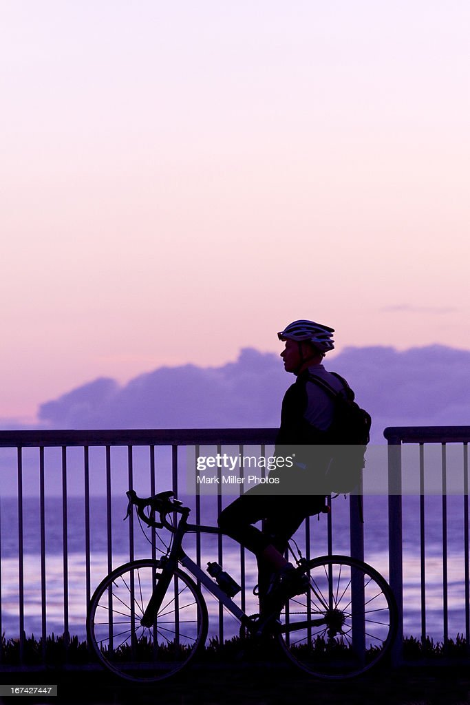Sunset Contemplation while Bicycling on Shoreline : Stock Photo