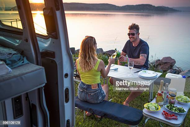 A sunset dinner at a lakeside campsite.