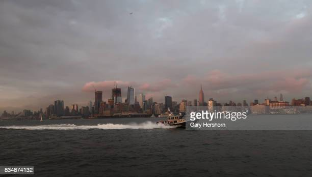 Sunset falls on midtown Manhattan and the Empire State Building in New York City as an NYPD boat patrols in the Hudson River on August 15 as seen...