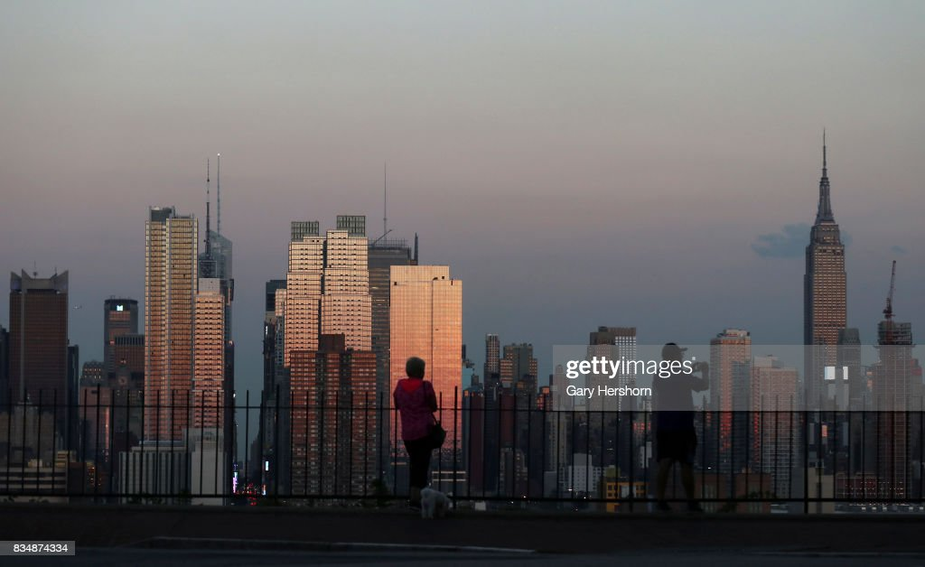 Sunset falls on midtown Manhattan and the Empire State Building in New York City on August 16, 2017, as seen from Weehawken, New Jersey.