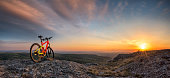 Beautiful sunset view with a mountain bike at the top of a hill