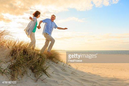 Puesta de sol y Feliz pareja madura en la playa