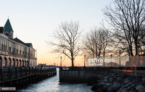 Sunset illuminates the Pier A Harbor House and desolate wintry tree at Battery Park New York.