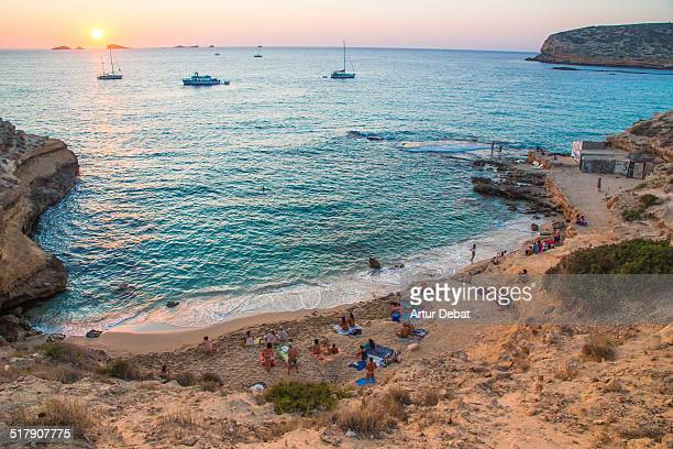 Sunset in Cala Compte beach with people in Ibiza.