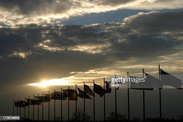 Sunset in cloudy sky beyond a row of flags