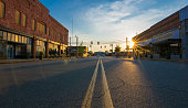 Storefronts at sunset in the middle of the road in downtown in a small Georgia town. The scene includes a low-angle view of the middle divider, sunburst at sunset, deep shadows and saturated colors.