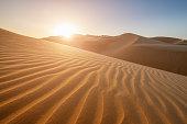 Sunset in the desert landscape, illuminating the rippled sand dunes, United Arab Emirates.