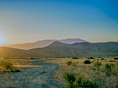 Sunset in the Nevada desert with a dusty dirt road and sagebrush covered mountains in the background.
