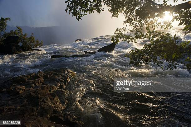 Sunset in the Victoria Falls Victoria Falls is the result of soft sandstone that fills huge cracks in the hard basalt rock of the plateau As the...
