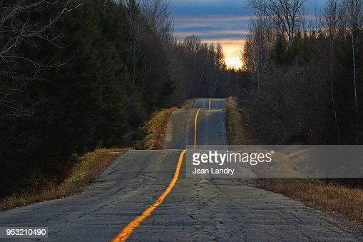 Sunset light on bumpy country road : Stock Photo