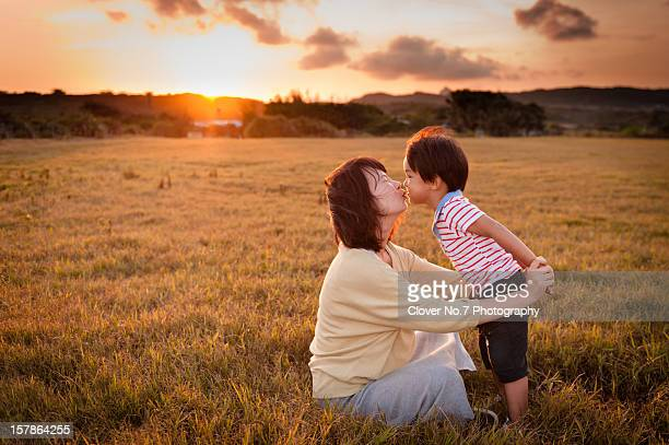 Sunset, mother and little boy kissing