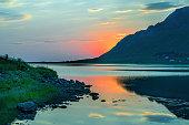 Sunset of midnight sun behind mountains at fjord of Lofoten, Norway