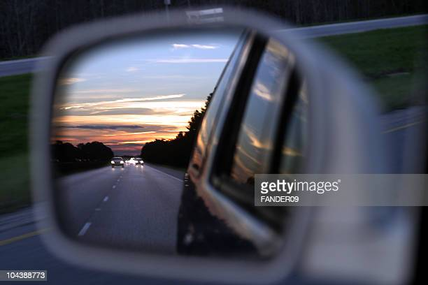 Sunset on a highway in the rear view mirror